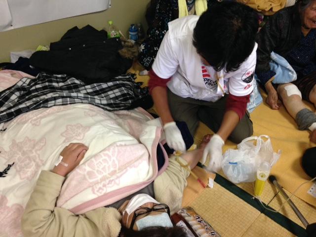 미나미-아소 내 하쿠수이 체육관에 마련된 대피소. 국경없는의사회 간호사 토모유키 하타이가 정맥 주사를 준비하고 있다. © Shumpei Tachi/MSF