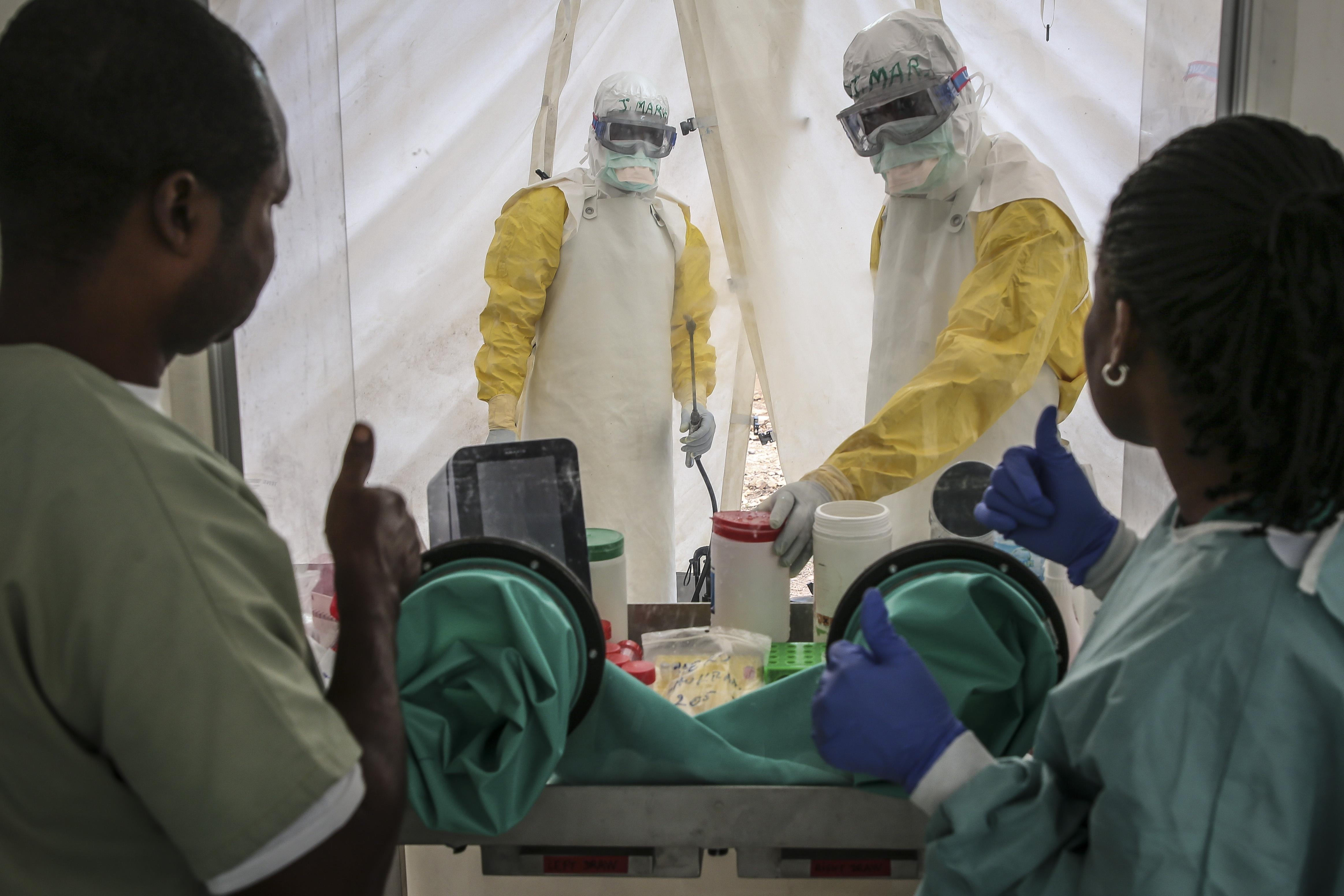 국경없는의사회 진단검사 전문가와 민주콩고 국립생체의학연구소(INRB) 일원이 검사실 고위험 구역에 있는 간호사 2명을 바라보고 있다. 민주콩고에서 에볼라 치료센터와 연구 검사실이 연계하여 활동하는 것은 이번이 처음이다. ⓒCarl Theunis/MSF